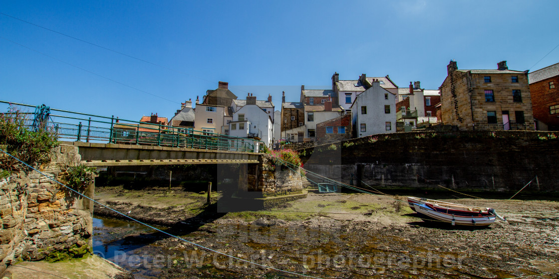 """""""Staithes Footbridge and Moored Fishing Boat in Staithes Beck, Yorkshire, England."""" stock image"""