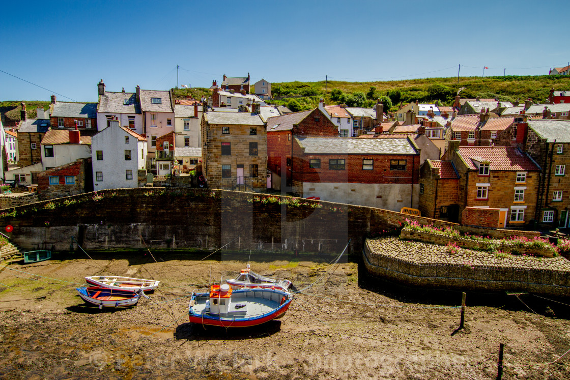 """""""Moored Fishing Boats in Staithes Beck, Cottages to the Background. Staithes, Yorkshire, England."""" stock image"""