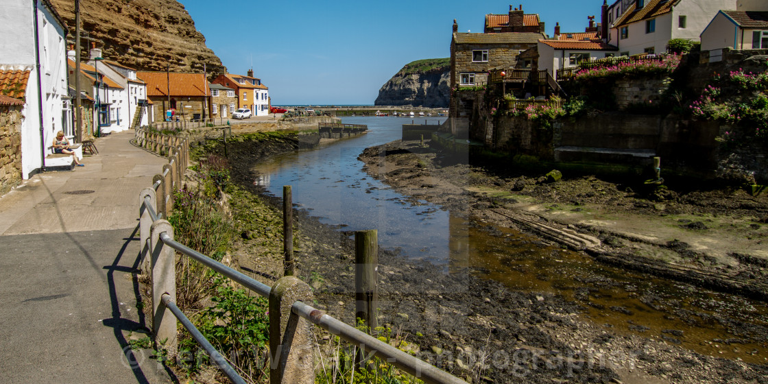 """""""View along Staithes Beck towards North Side Cottages, Cowbar Nab and the Harbour. Yorkshire, England."""" stock image"""