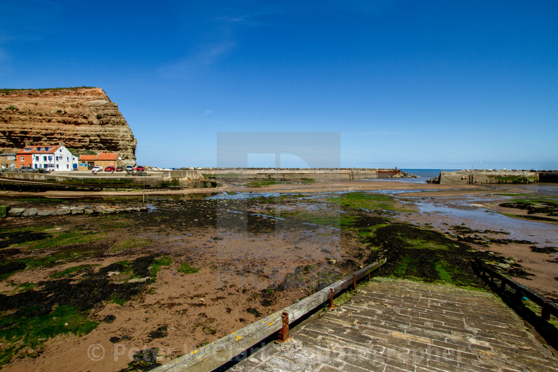 """""""Staithes, Cowbar Nab and Harbour at Low Tide, Slipway to the foreground, Yorkshire, England."""" stock image"""