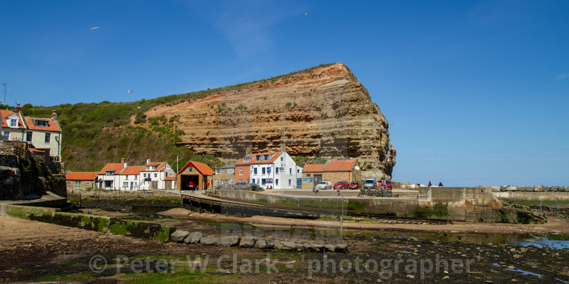 """""""Staithes Harbour at Low Tide, Cowbar Nab in the Background, Yorkshire, England."""" stock image"""