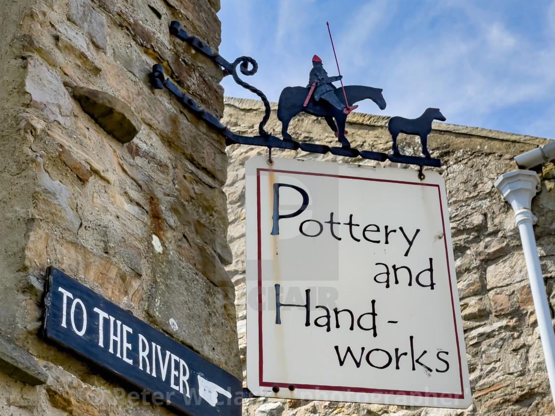 """""""Pottery and Handworks corner shop sign, Reeth, Swaledale. Also To The River direction sign."""" stock image"""