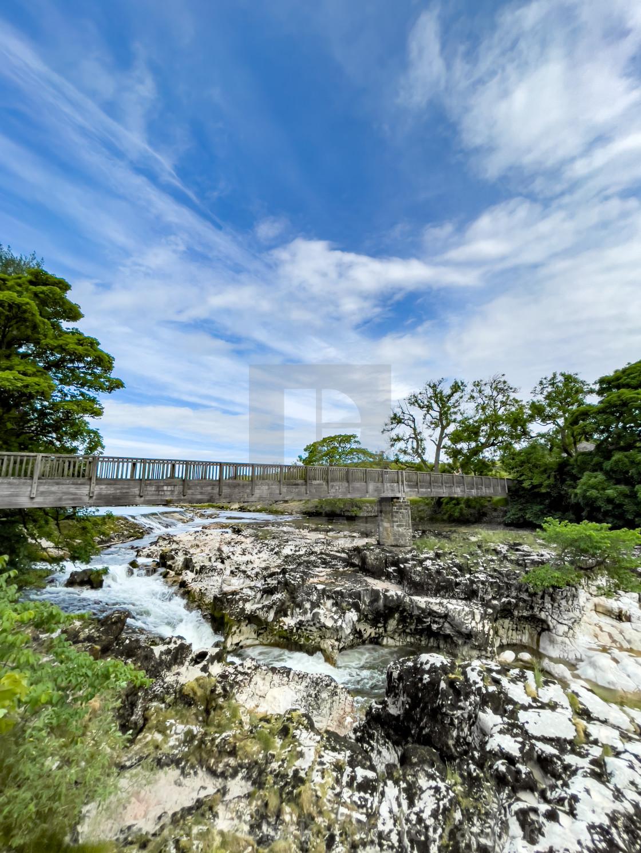 """Linton Lower Falls and Footbridge, River Wharfe."" stock image"