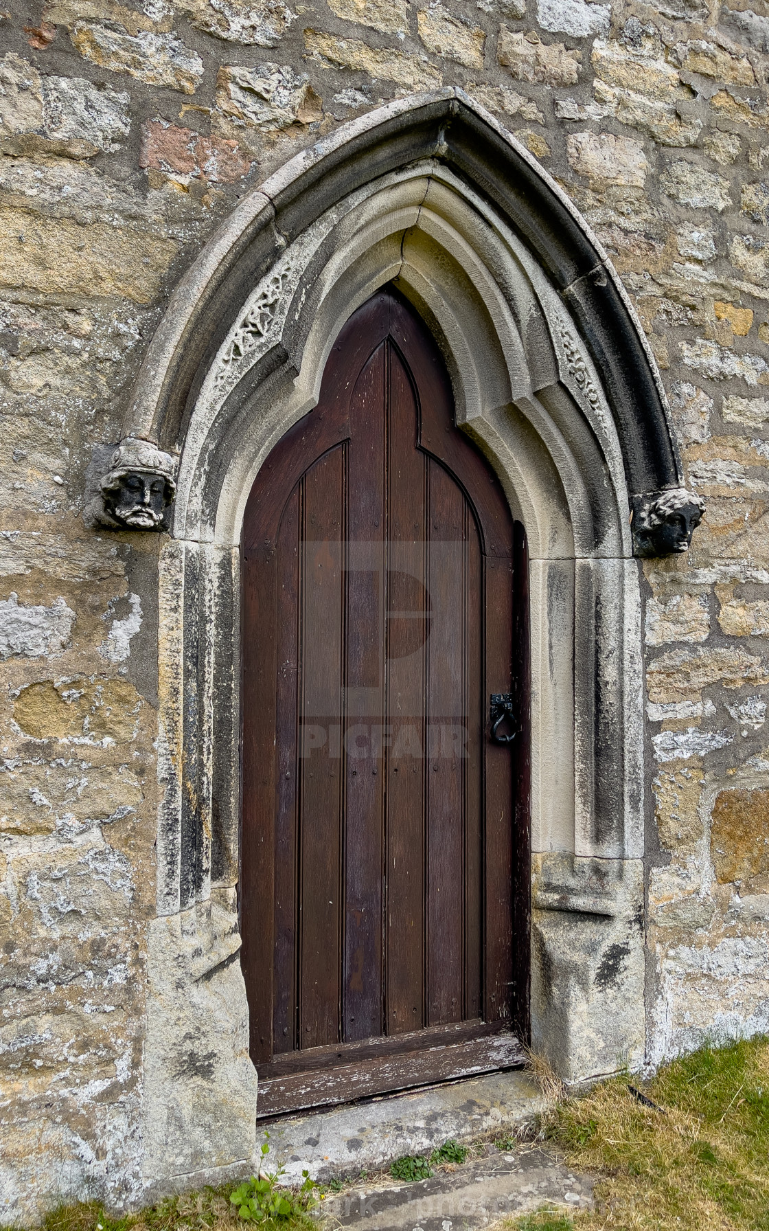 """""""Side Door and Carved Heads, Parish Church, St Michael and All Angels, Linton in Craven."""" stock image"""