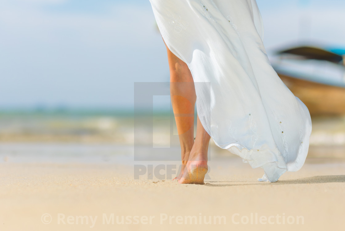White pareo woman legs walking on tropical beach vacation. Close