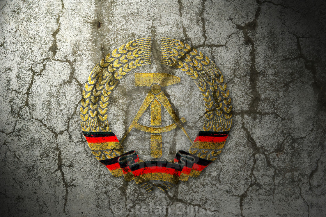 """national symbol of German Democratic Republic (GDR) on a cracked wall"" stock image"