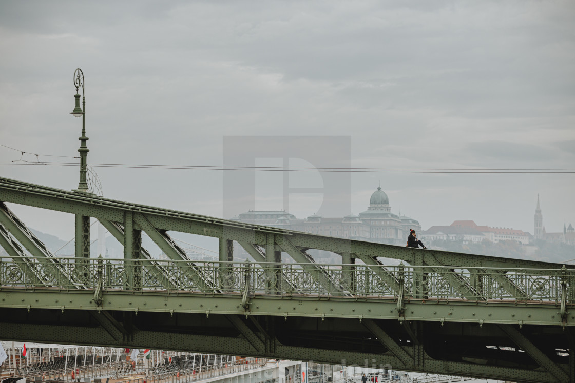 """""""Sitting and smoking girl on the top of the green Liberty bridge above the Danube river in Budapest"""" stock image"""