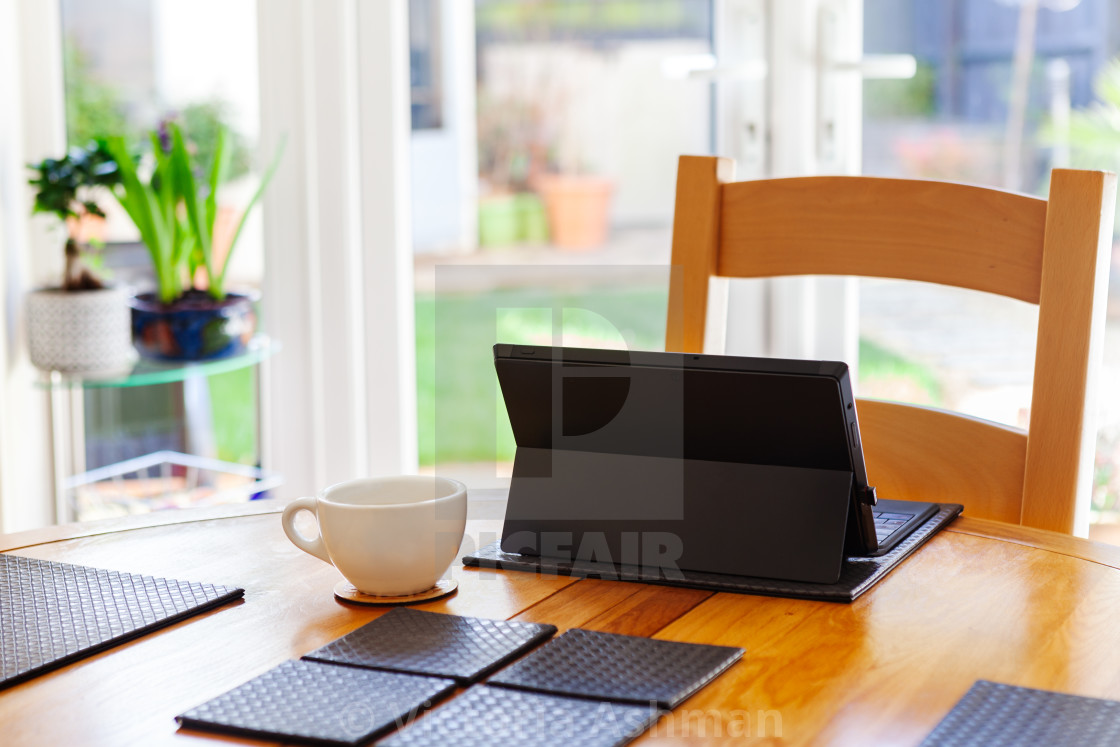 """""""Working from home, kitchen table with a small laptop and coffee"""" stock image"""