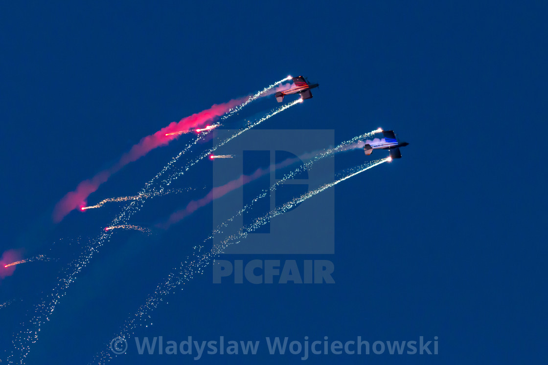"""Aerobatic team performing night aerobatics with fireworks"" stock image"