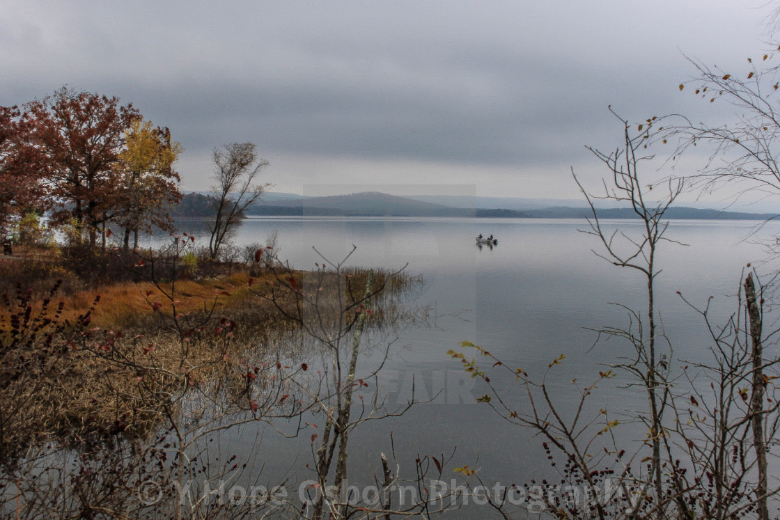 """""""a serene autumn tree lined shore of lake with fishermen"""" stock image"""