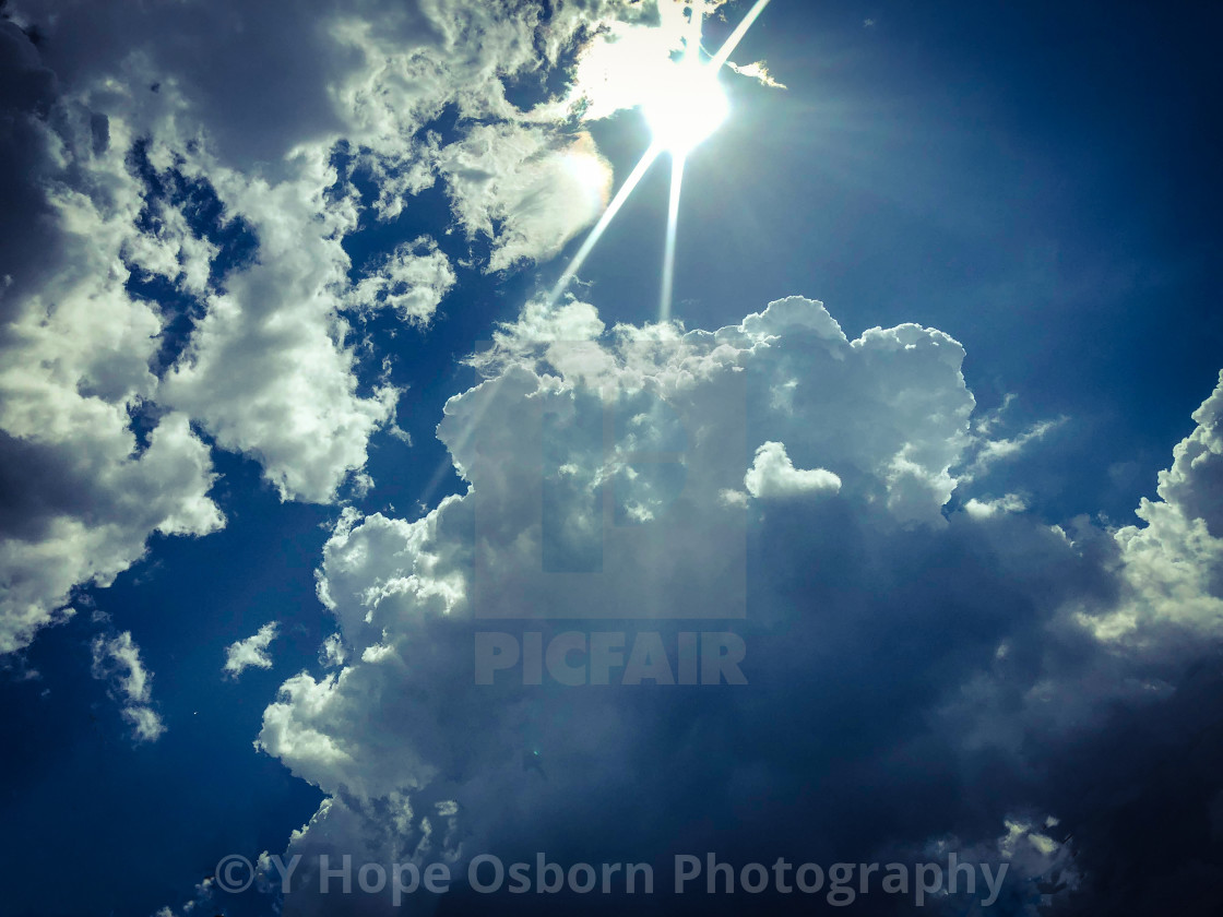 """""""blue cloudy sky with sun flare"""" stock image"""