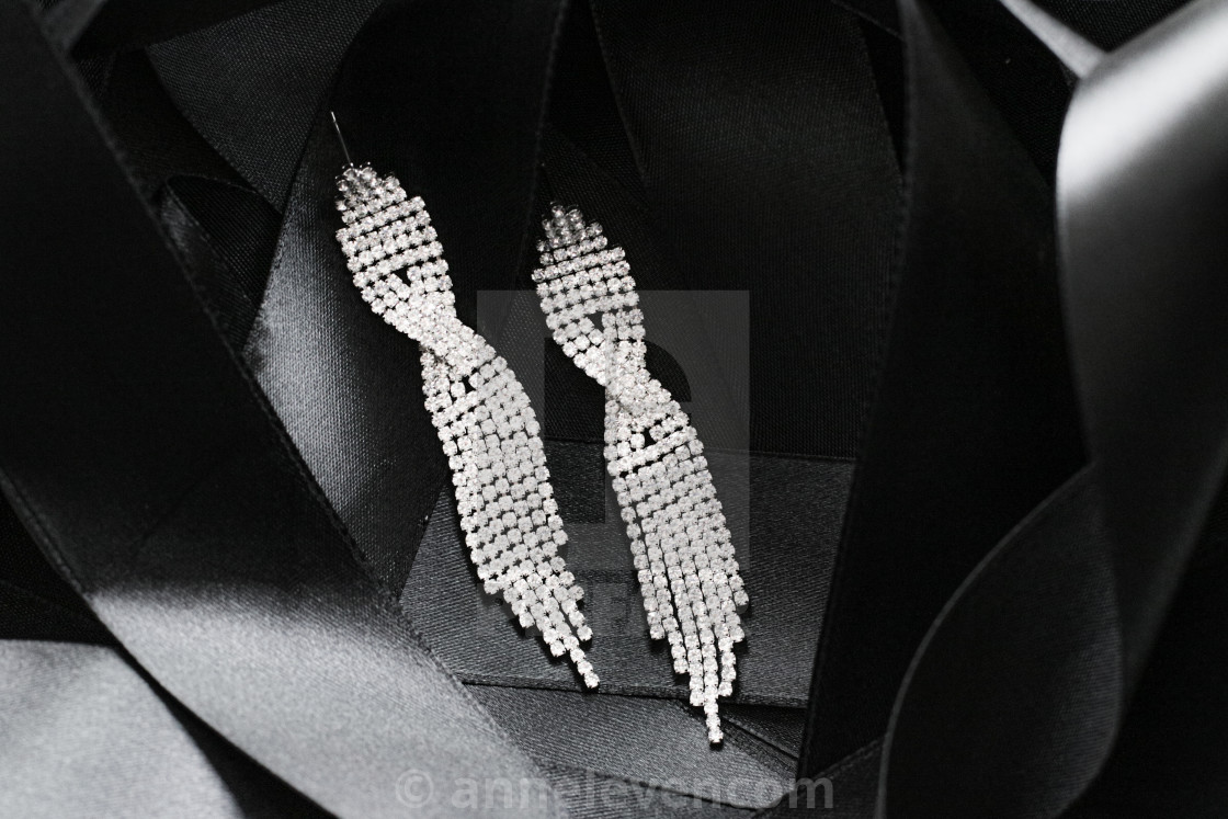 """Luxury diamond earrings on black silk ribbon as background, jewe"" stock image"