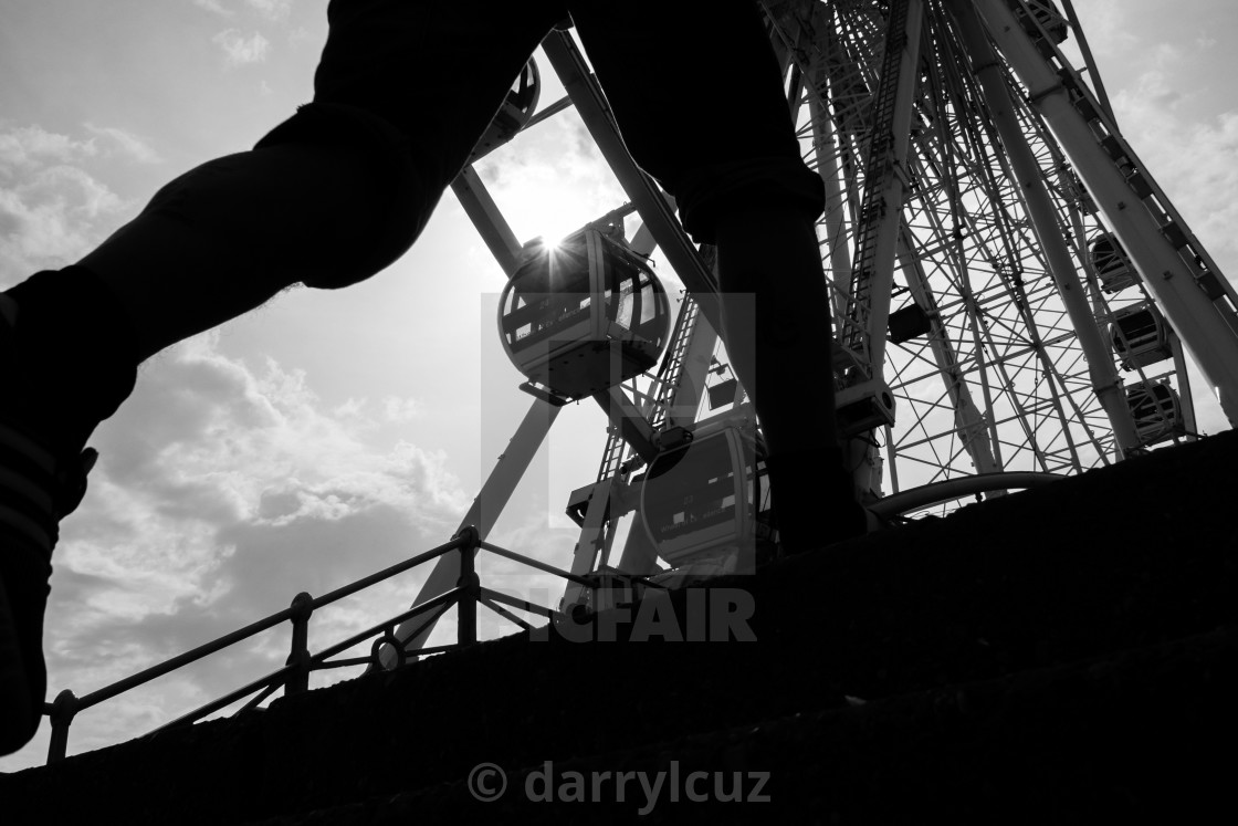 """""""Low angle street shot of The Big Wheel seen through a passer by's legs in Brighton, UK."""" stock image"""