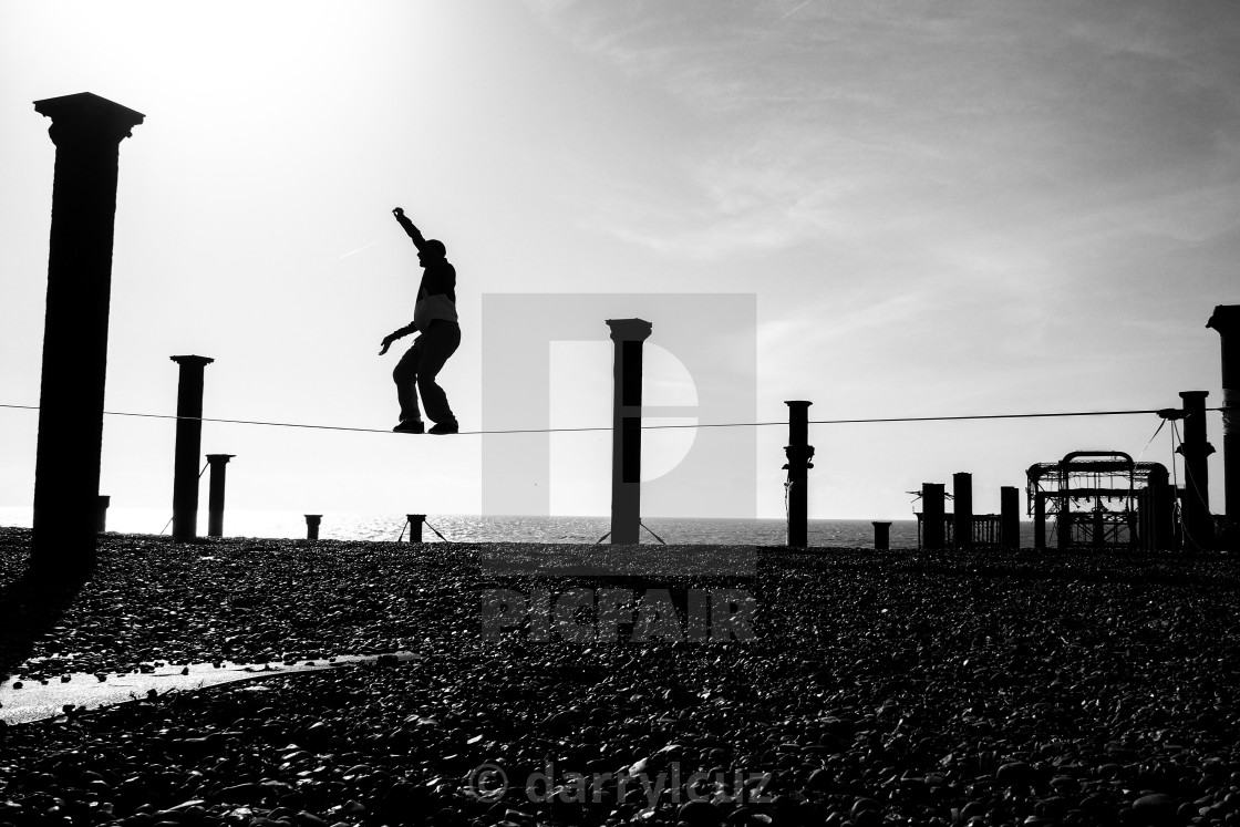 """Silhouette of a tightrope walker in front of the ruin of The West Pier in Brighton, UK."" stock image"