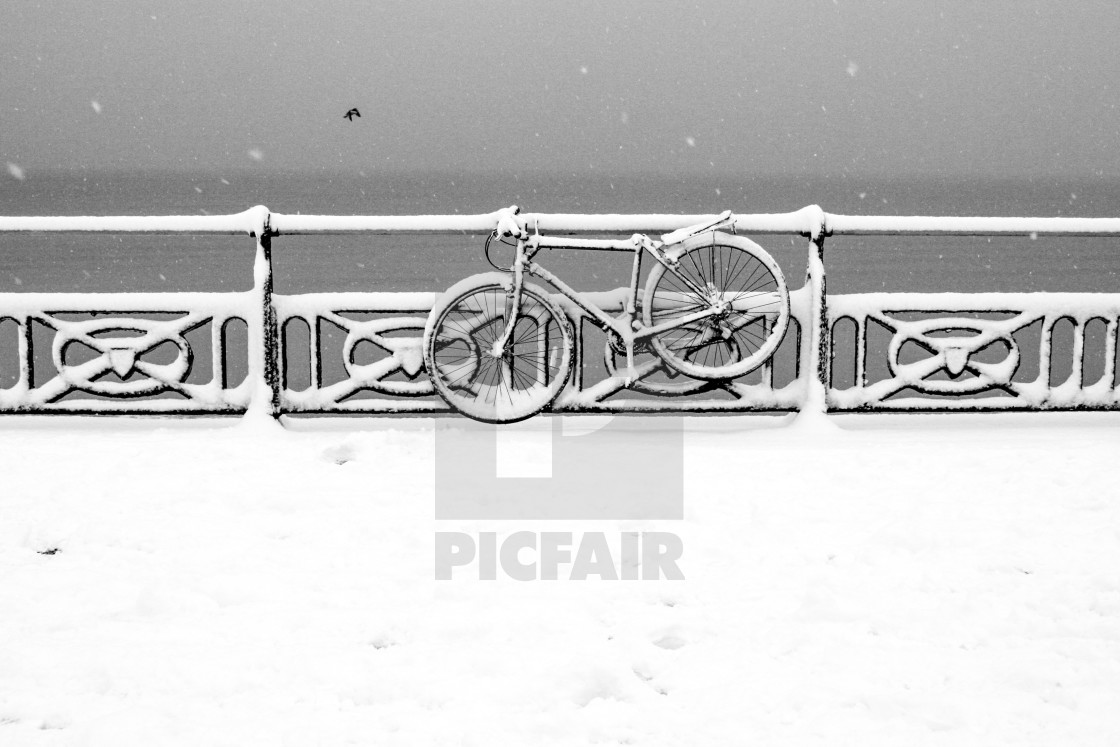 """""""A bycycle covered in snow chained to the railings on the promenade in Hove, UK."""" stock image"""