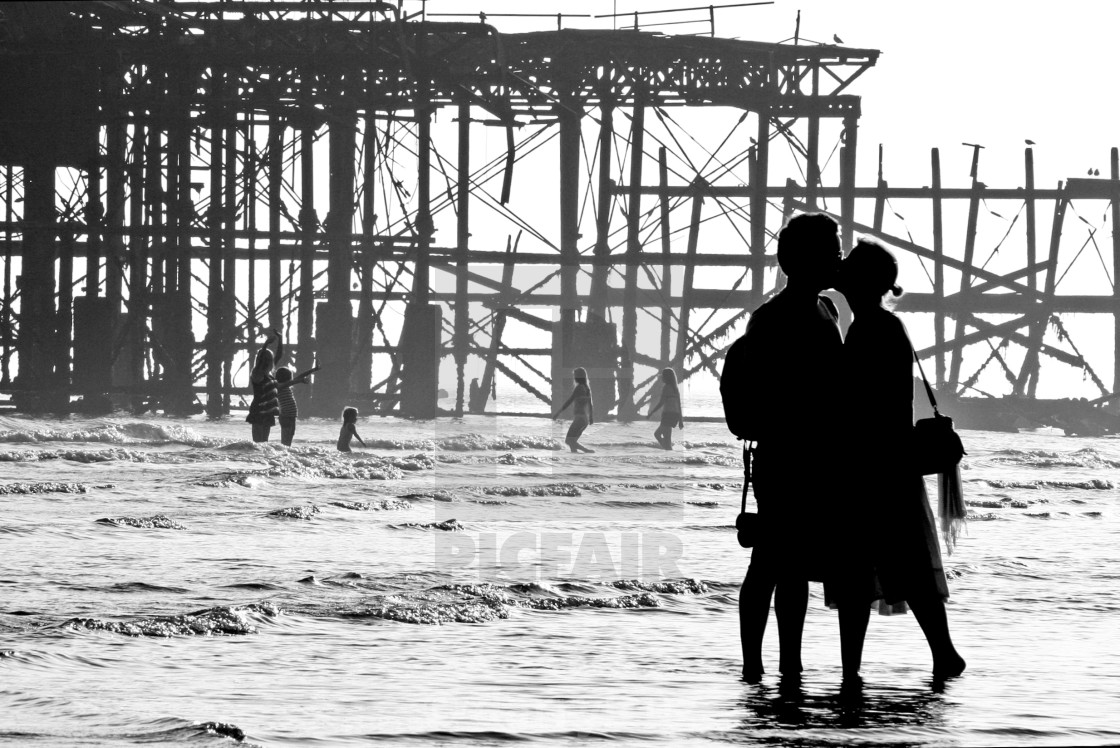 """A couple kiss in silhouette in front of the ruin of the West Pier at low tide in Brighton, UK."" stock image"
