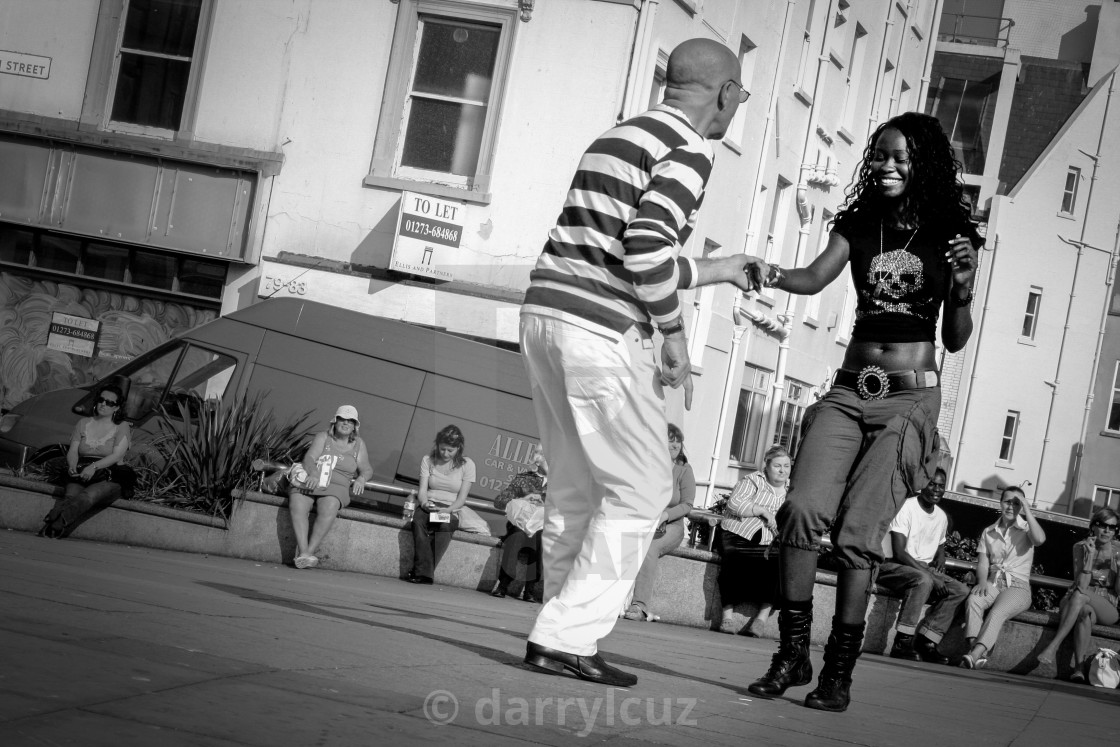 """Angled shot of a man dancing with a young girl in the street at Brighton in the UK."" stock image"