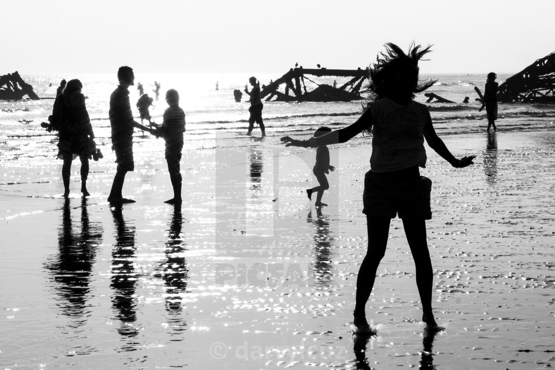 """A girl dancing in silhouette with various other people in front of the Ruin of The West Pier at low tide in Brighton, UK."" stock image"