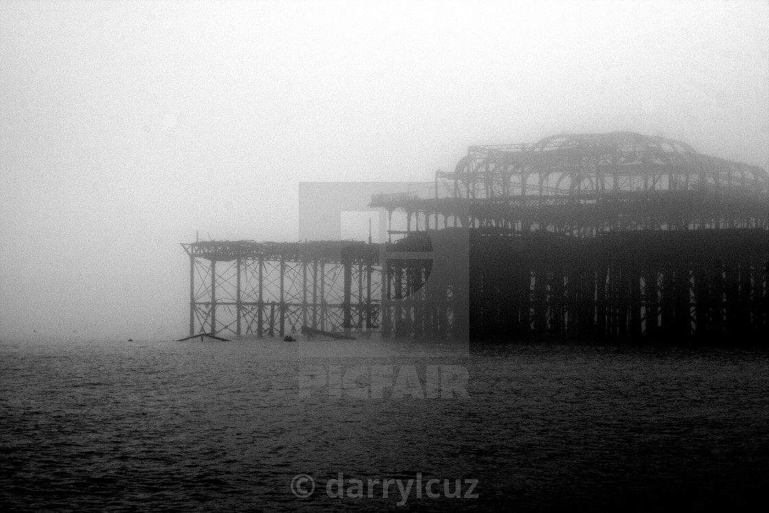 """The ruin of the Victorian West Pier seen through the mist in Brighton, UK."" stock image"