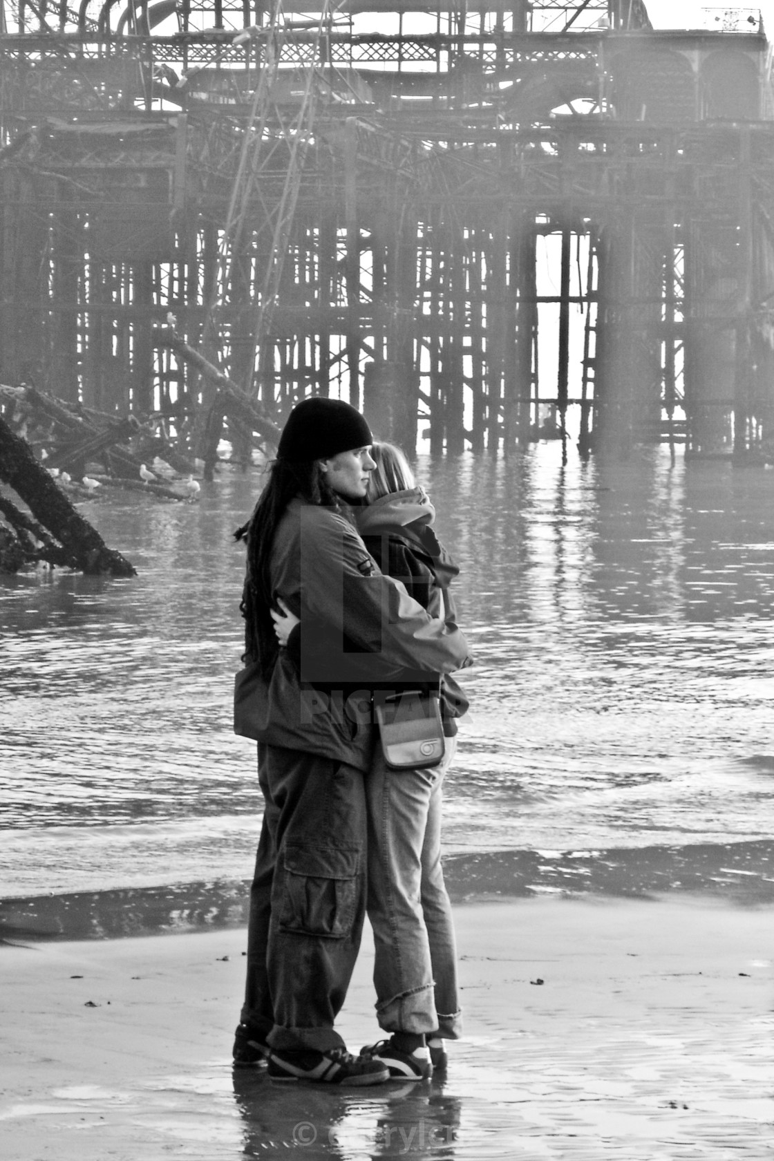 """A couple Embrace in front of the wreck of the west pier in Brighton."" stock image"