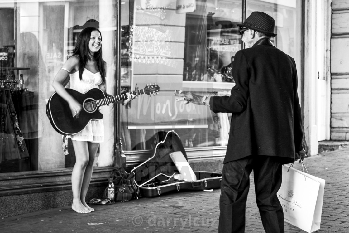 """""""A girl busking in bare feet in the street shares a joyous moment with a well dressed, elegant man in Brighton, UK."""" stock image"""