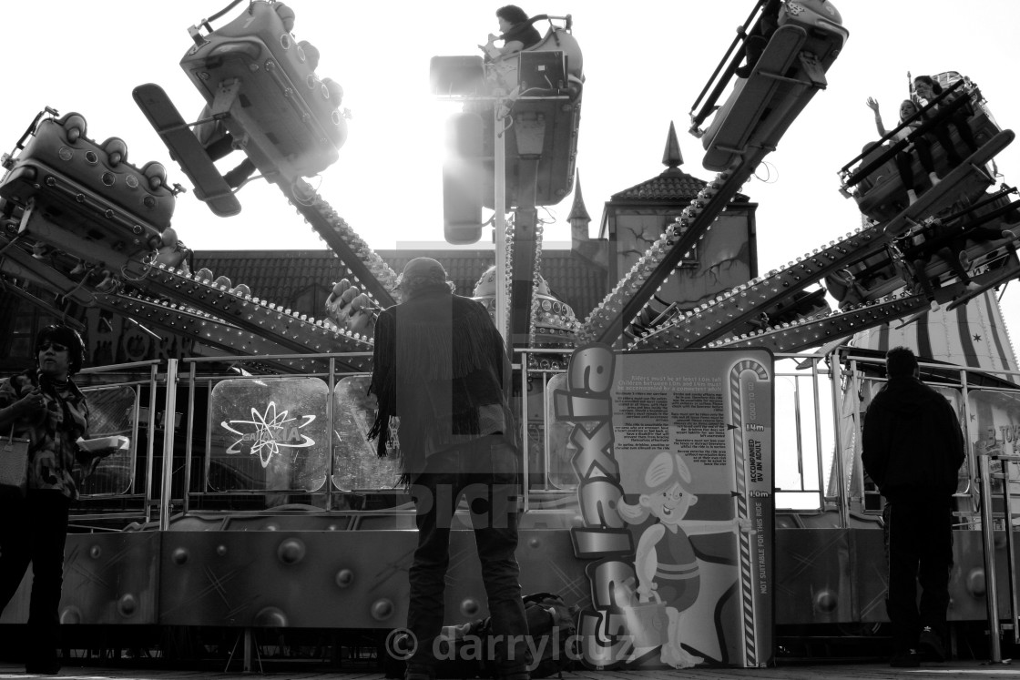 """""""Street shot of a man dancing in front of the Galaxia ride on The Palace Pier in Brighton, UK."""" stock image"""