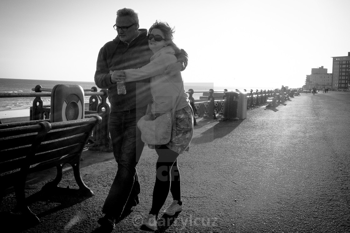 """""""A couple hold onto each other in strong winds on Hove promenade in the UK."""" stock image"""