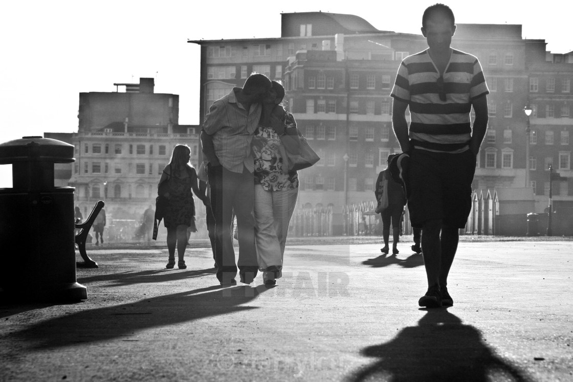 """""""Street shot of a couple kissing on the promenade at dusk in Hove, UK."""" stock image"""