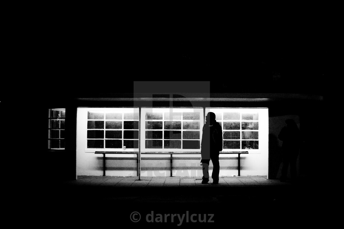 """Night shot of a man in silhouette waiting at a bus stop in Brighton, UK."" stock image"