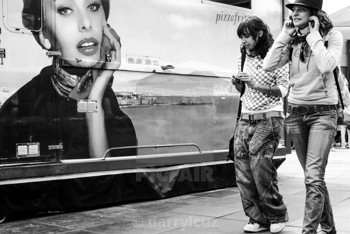 """""""A amn carryingTwo girls in street wear wander past a picure of Sophia Loren on a pizza van in Brighton, UK."""" stock image"""