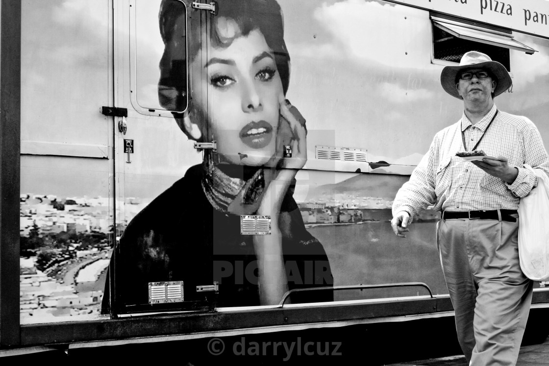 """""""A amn carrying a pizza wanders past a picture of Sophia Loren on a pizza van in Brighton, UK."""" stock image"""