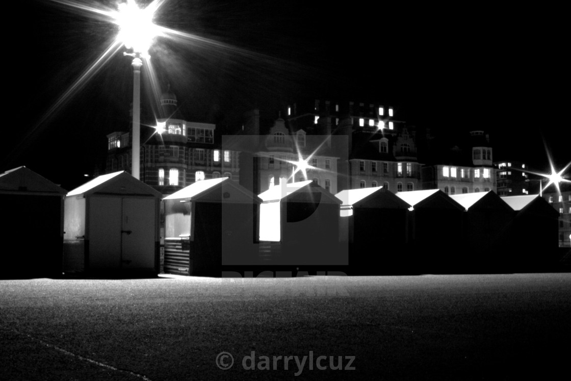 """""""A row of beach huts at night with a single street light on Hove promenade, UK."""" stock image"""