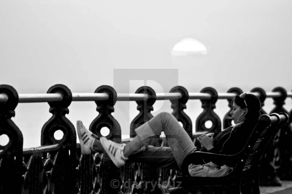 """A girl smoking a cigarette on a bench with the the sun behind on Hove promenade, UK."" stock image"