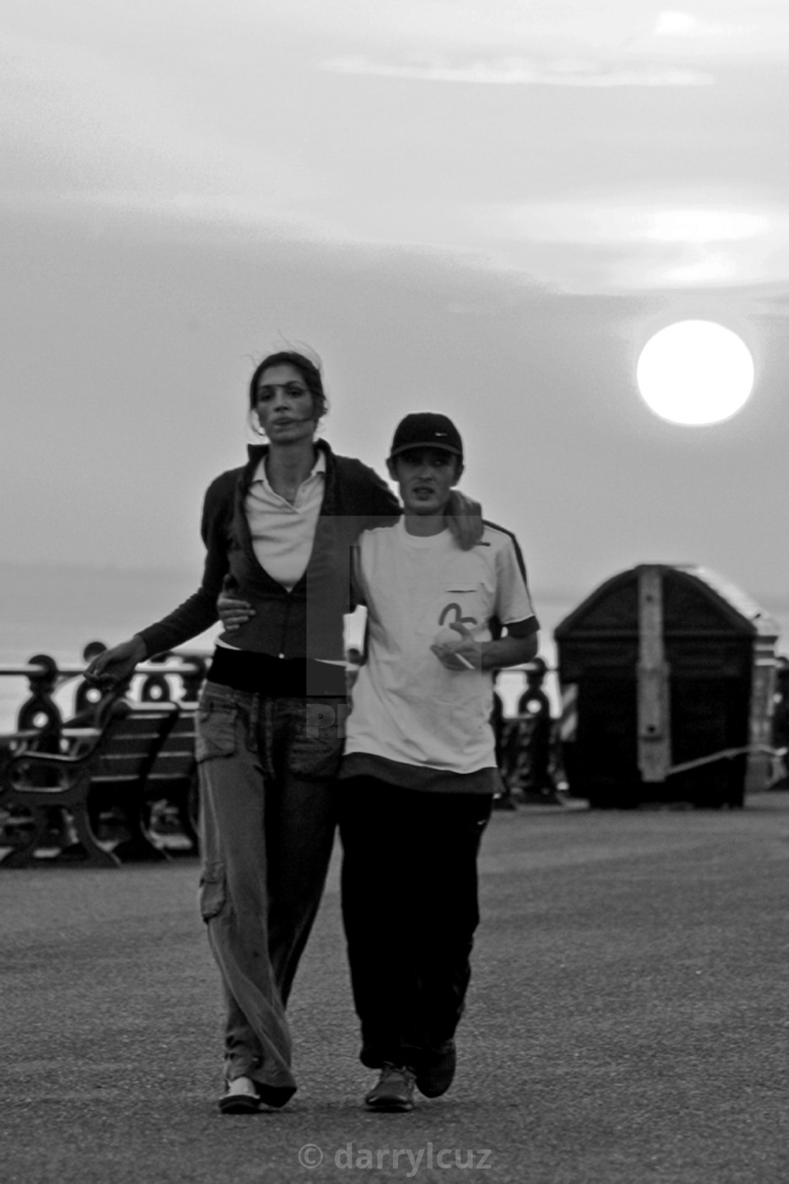 """""""A couple walking along the promenade in Hove with the sun setting behind."""" stock image"""