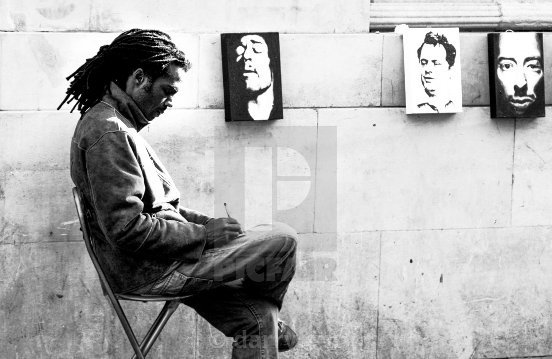 """Street shot of an artist selling portrait paintings in The North Laine, Brighton, UK."" stock image"