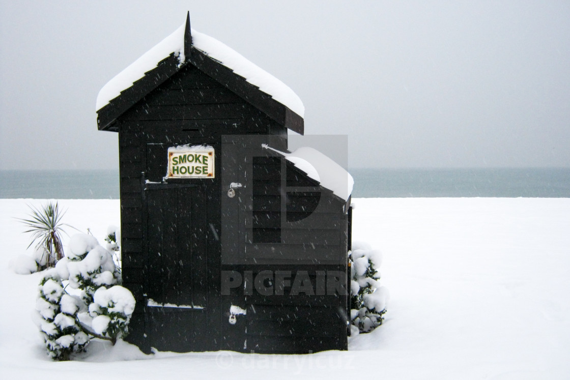 """""""A smoke house in the snow on Brighton beach in the UK."""" stock image"""