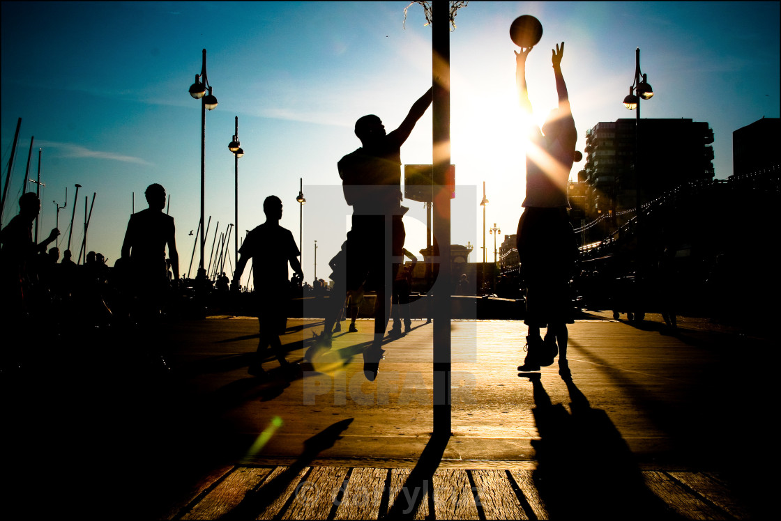 """""""Silhouette of basketball players on Brighton seafront in the UK."""" stock image"""