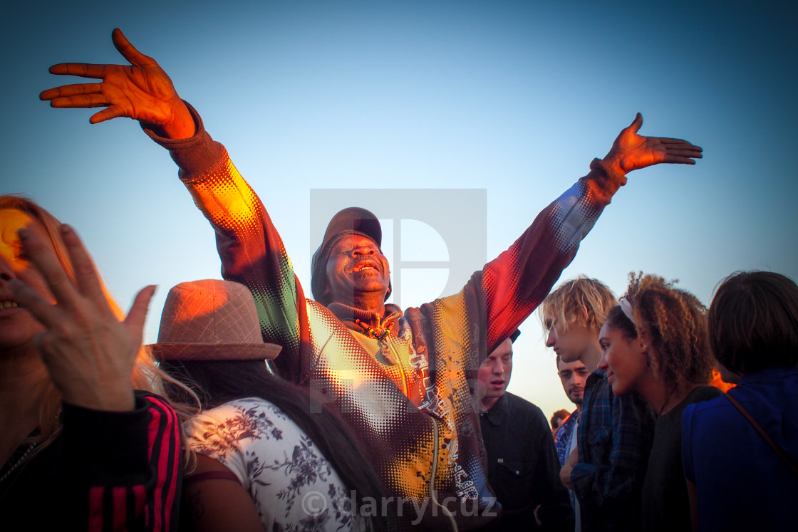 """""""Man in brightly coloured coat enjoys the music at a Reggae Festival in Hove, UK."""" stock image"""