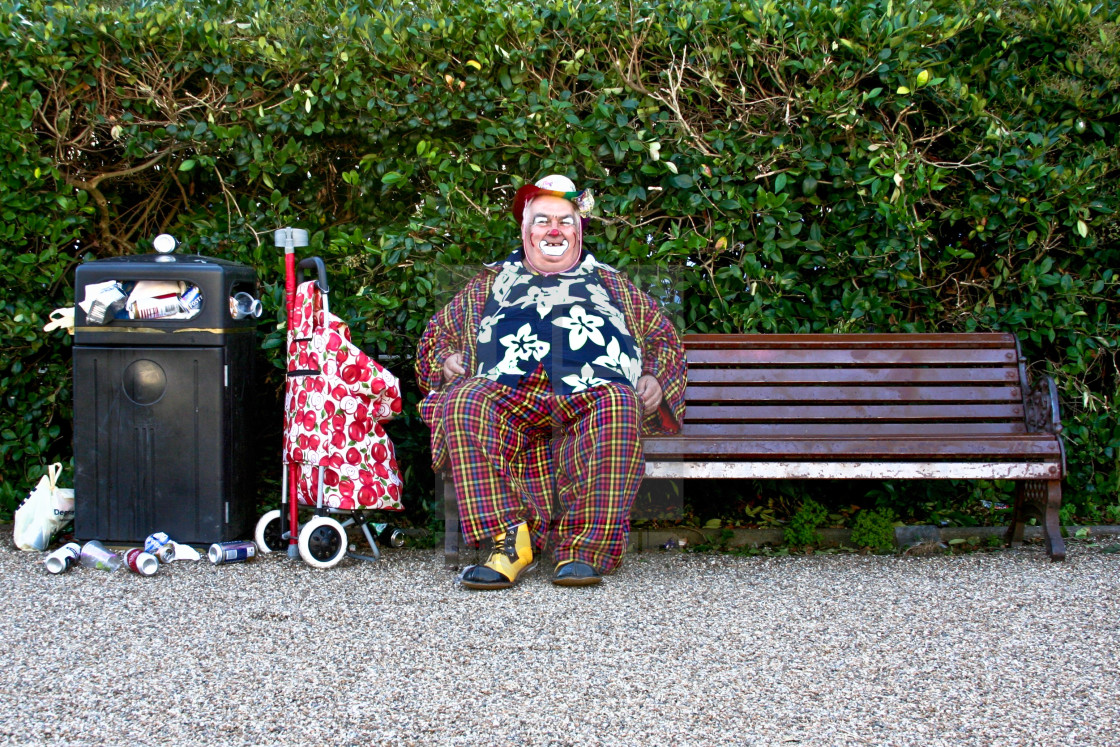 """""""Clown sitting on a bench with a bin full of rubbish in Hove, Brighton."""" stock image"""