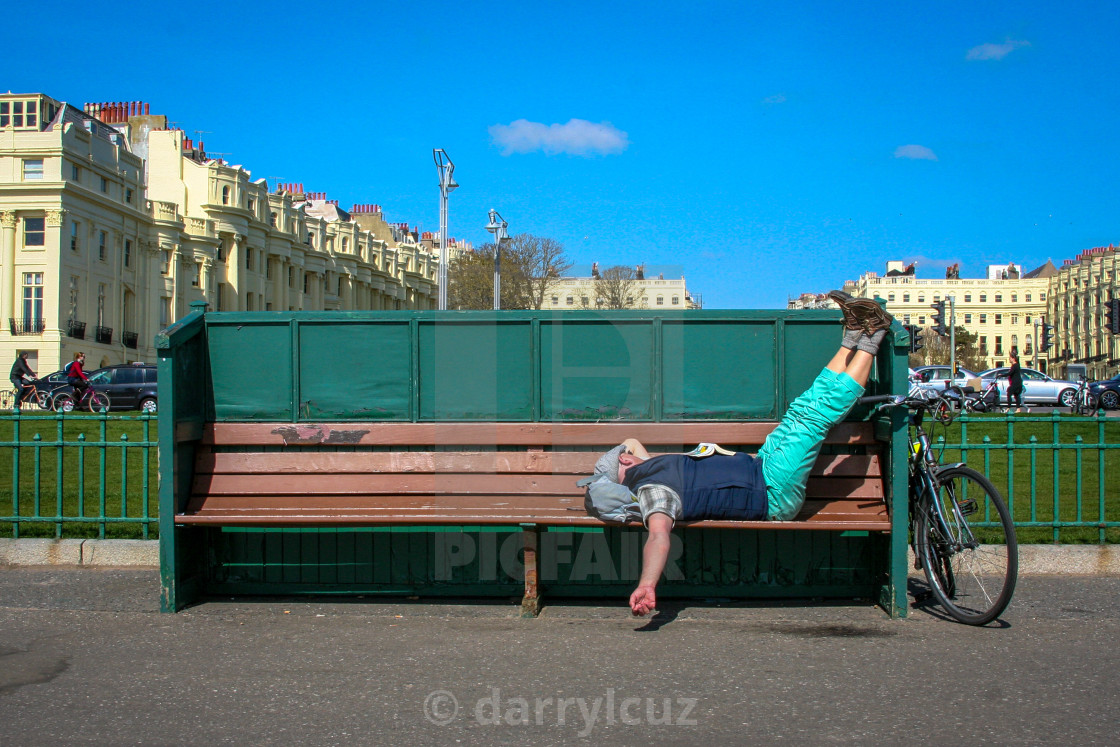 """""""A man asleep on a bench with his bycycle beside him in Hove, UK."""" stock image"""