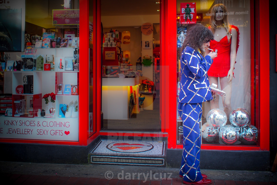 """""""Eccentric man in colourful suit in front of kinky shop in The North Laine, Brighton, UK"""" stock image"""