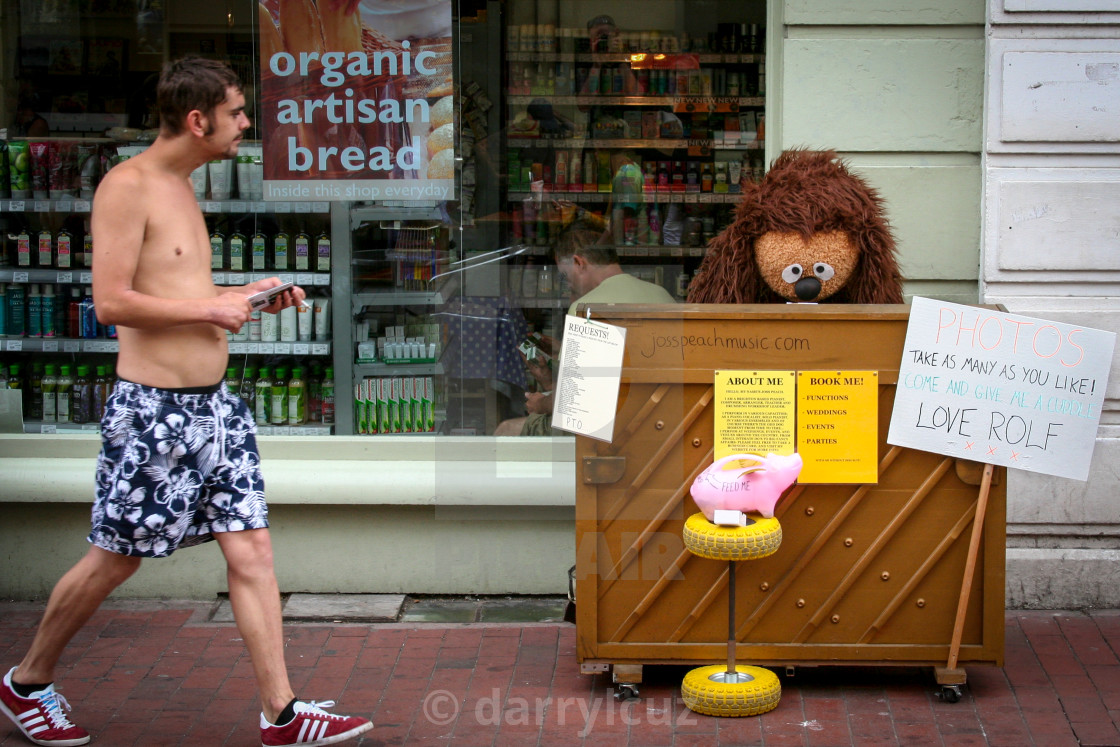 """""""A man dressed in a muppet suit plays the piano on the street in The North Laine in Brighton, UK."""" stock image"""