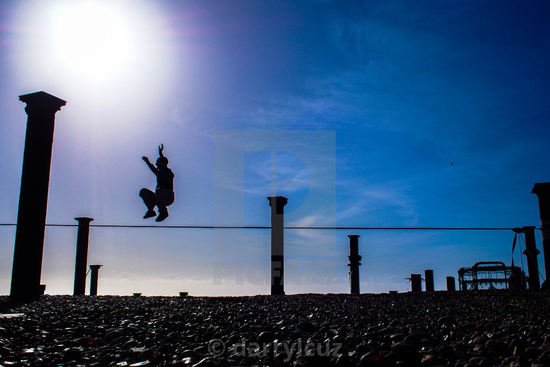 """""""A man walking a tightrope on the beach in Brighton, UK."""" stock image"""