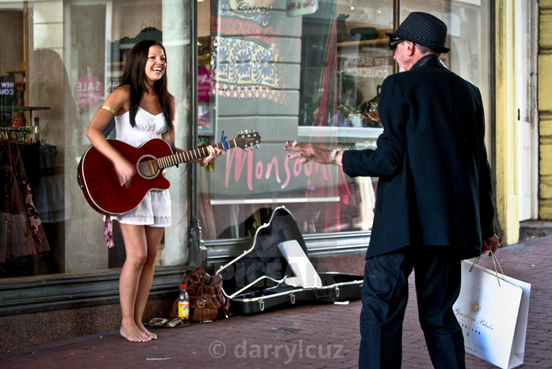 """A girl busking in bare feet with a well dressed man in Brighton, UK."" stock image"