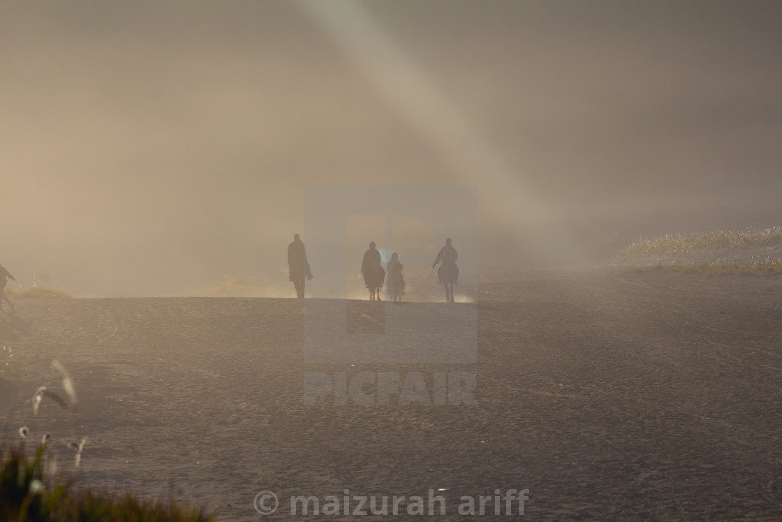"""silhouettes if horsemen on Bromo desert"" stock image"