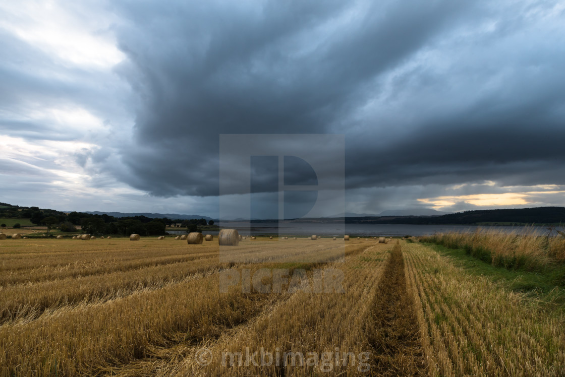 """""""Storm clouds roll over a harvested field"""" stock image"""