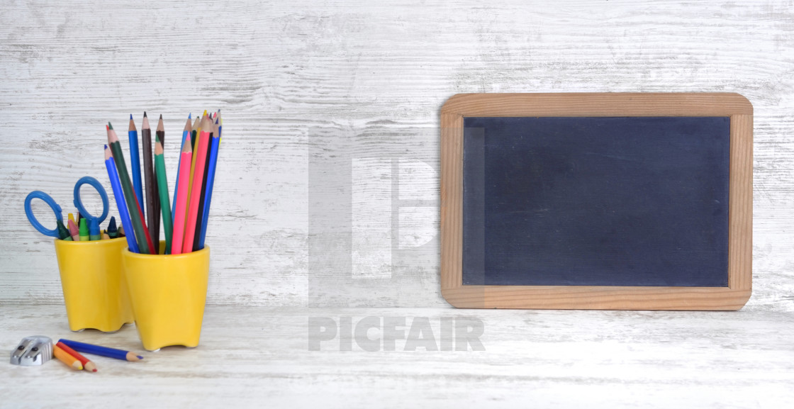 """""""slate on a white desk with colorful pencils in yellow pot with empty space to message"""" stock image"""