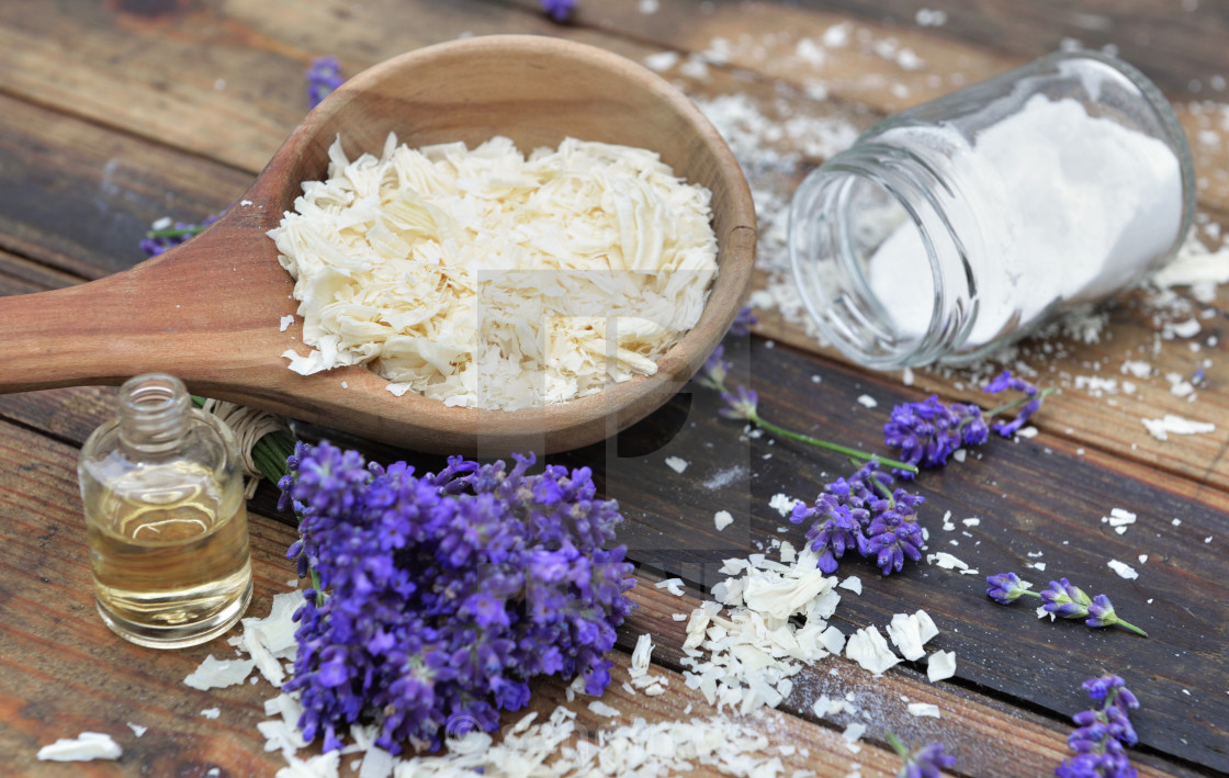 """""""spoon full of flakes of soap with essential oil and bunch od lavender flowers and sodium bicarbonate on wooden background"""" stock image"""