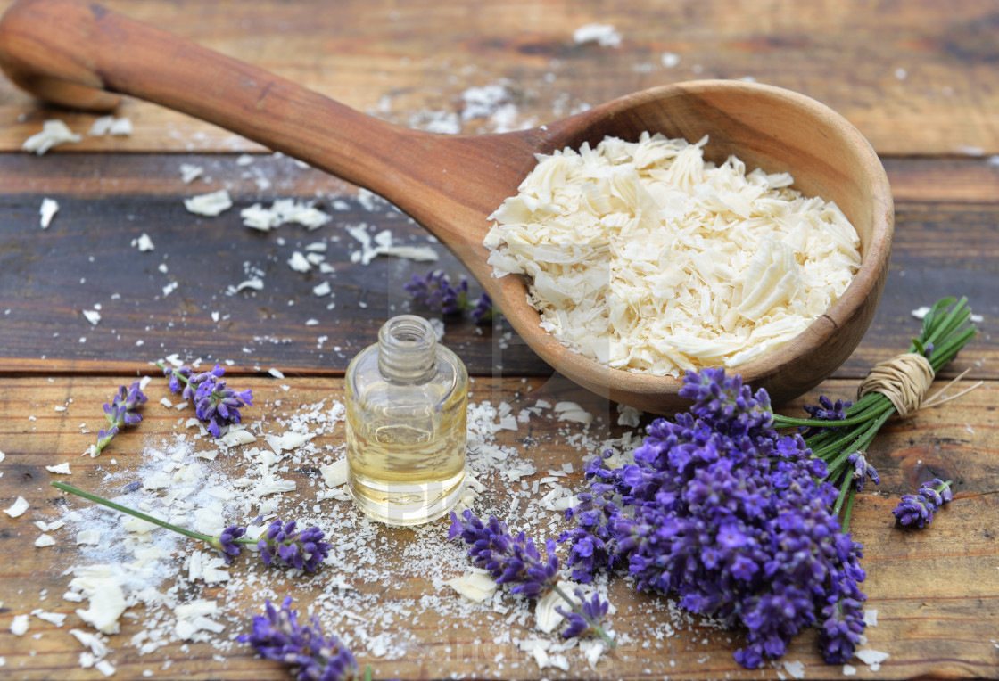 """""""spoon full of flakes of soap with essential oil and bunch of lavender flowers on wooden background"""" stock image"""