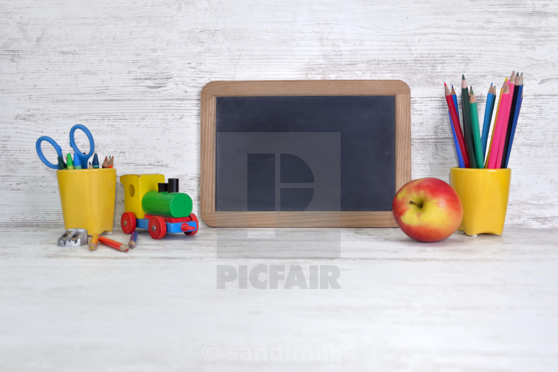 """""""slate on a kid desk with colorful pencils in yellow pot and an apple"""" stock image"""